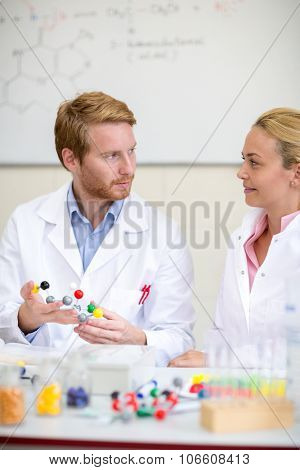 Chemical professor show molecular model to young female assistant
