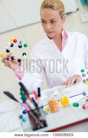 Young female chemistry teacher observing molecular structure in classroom