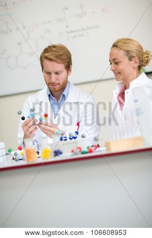 Professor and his assistant studying molecular model in chemical cabinet