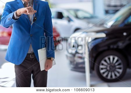 car agent  in car dealership saloon holding car key in front of him