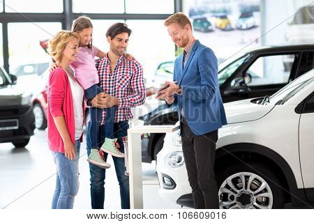 Car dealer offering a car to young  smiling family