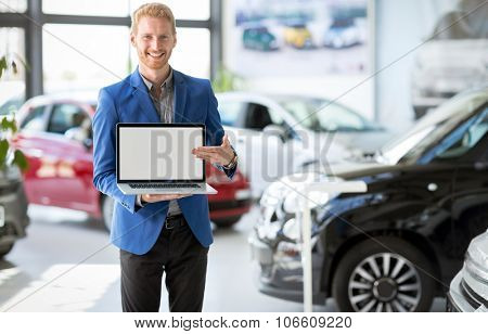 Cheerful car agent holding open laptop and pointing in the empty screen