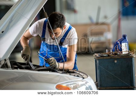 Auto mechanic working under the hood in garage