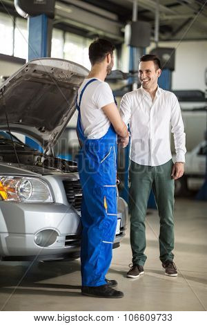 smiling auto mechanic and client shaking hands in sevice