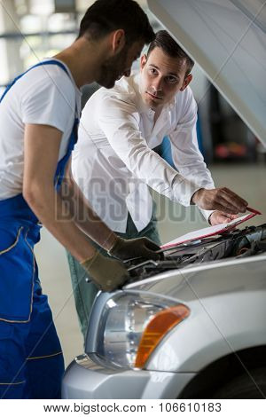 manager and mechanic examine a car damage