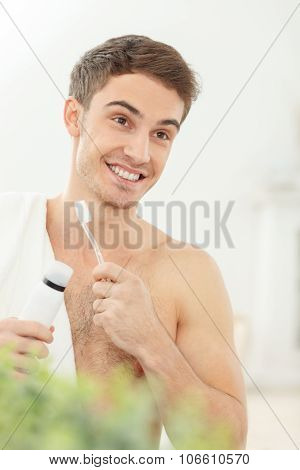 Attractive guy is preparing himself for a date