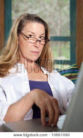 Serious Stern Woman At Laptop Computer Looking At Camera