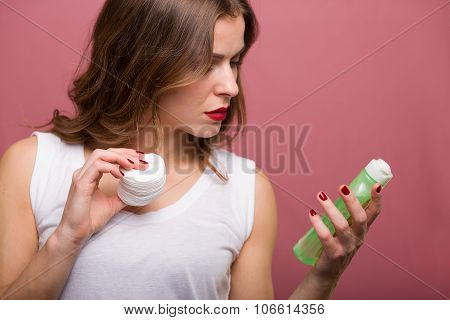 Woman Holding A Lotiona And A Cotton Pad