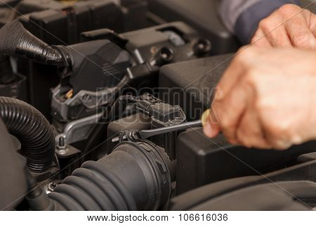 Cheerful male technician is repairing the vehicle