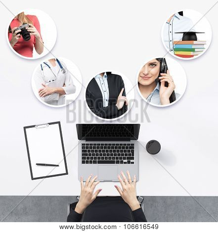 Top View Of The Working Place With Woman's Hands. A Laptop, Notepad And A Cup Of Coffee Are On The T