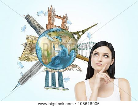 A Brunette Woman Thinks About Travelling. A Globe With Sketched Famous Places. Light Blue Background