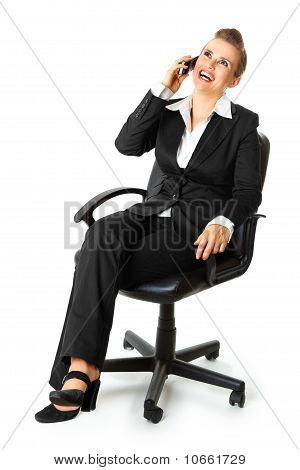 Successful modern business woman sitting on chair and talking on mobile phone