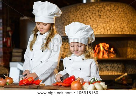 Smiling Chef girls preparing healthy food vegetable salad at restaurant kitchen