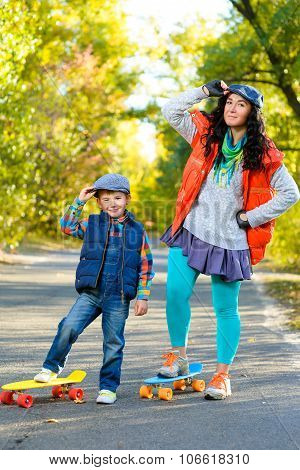Smiling woman and boy standing on color plastic penny board skateboard at park