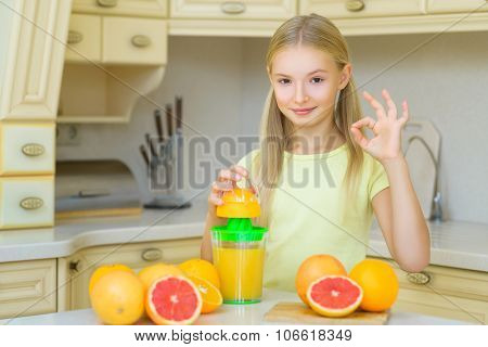 Child with oranges. Girl squeezed fresh orange juice and showing Ok
