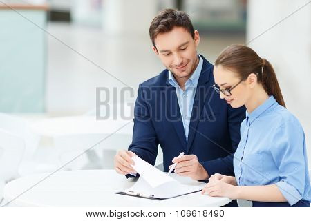 Nice-looking colleagues doing office paperwork
