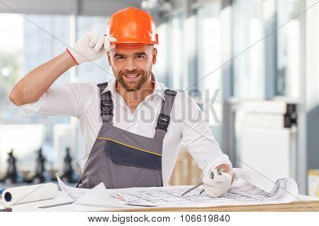 Cheerful engineer is creating plan of building