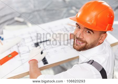 Cheerful male builder is working on new construction