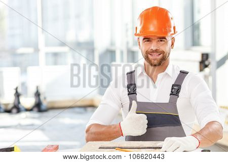Attractive male builder is working with wooden material
