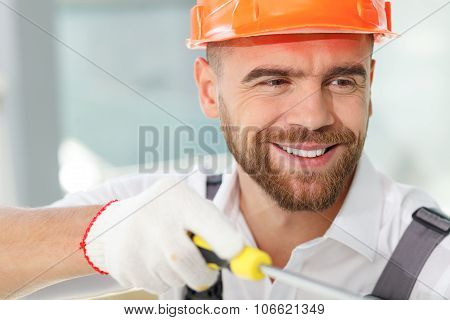 Handsome young builder is installing furniture in house