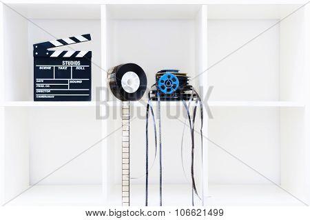 Movie Clapper Board And Film Reels On White Bookshelf
