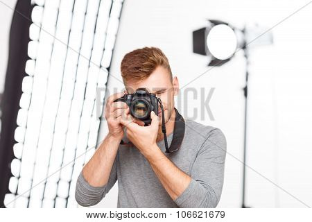 Handsome male professional upholds his camera.