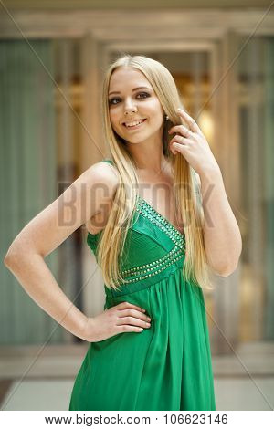 Romantic young blonde woman in green sexy dress, indoor