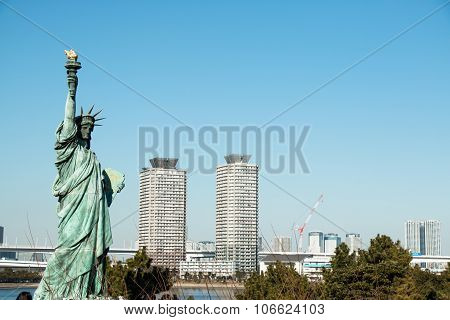 Lady liberty juxtaposed stand against Rainbow Bridge in Tokyo, Odaiba in Japan