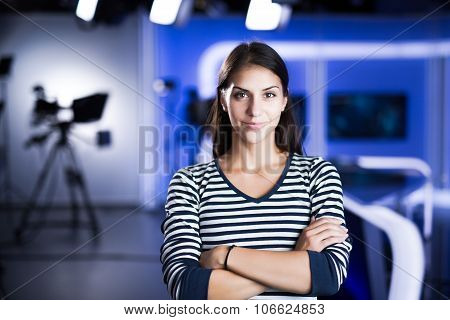 Young beautiful brunette television announcer at studio standing next to the camera.TV director