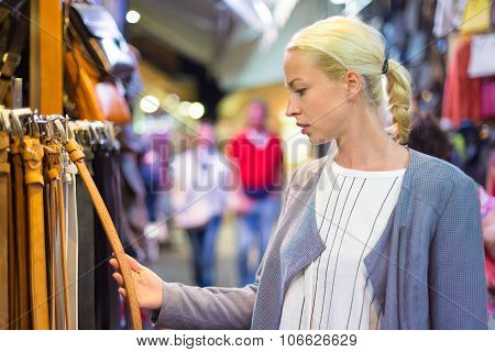 Casual blond woman shopping for leather belt.