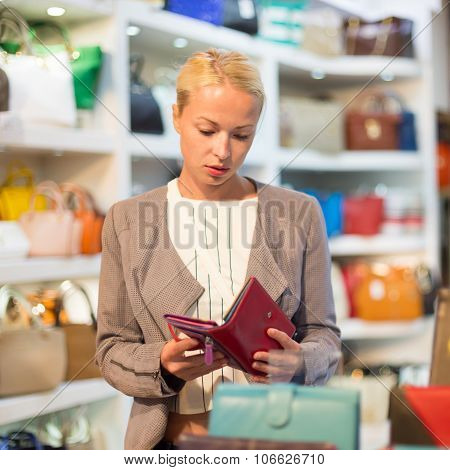 Casual blond woman shopping for leather wallet.