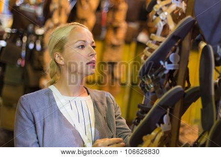 Casual blond woman shopping for leather sandals.