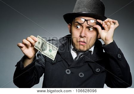 Young man in black coat holding money against gray