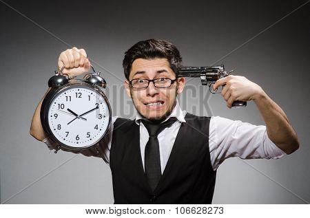 Employee holding alarm clock and handgun against gray