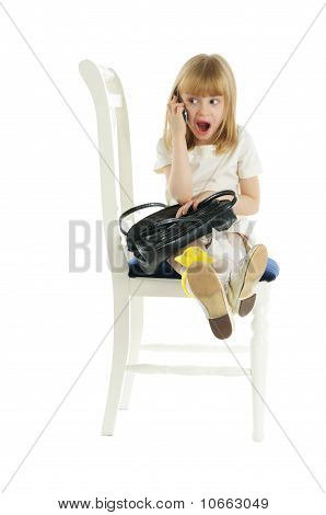Surprised girl with phone on chair