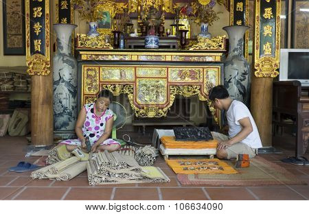 Senior craftsmen making printed painting artwork in traditional way in Dong Ho village