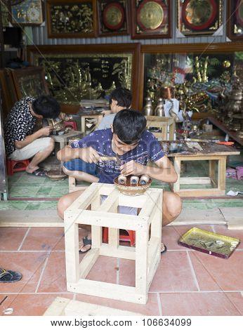 Junior craftsmen making copper handicraft products in traditional way