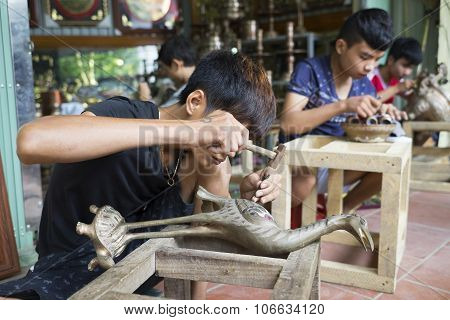 Junior craftsmen making copper handicraft products in traditional way