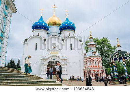 People walking near Dormition - Assumption Cathedral. Built in 1559 - 1585 in the Trinity Lavra of S