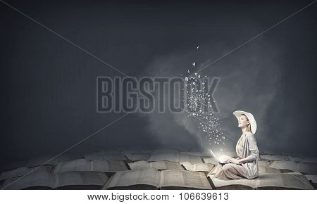 Woman in dress and hat sitting on books and working on laptop