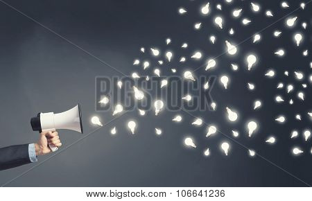 Hand holding megaphone and light bulbs flying out of it