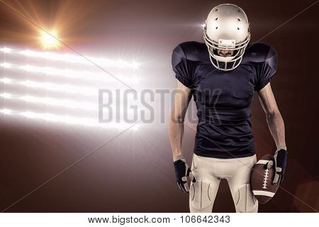 American football player looking down against spotlights
