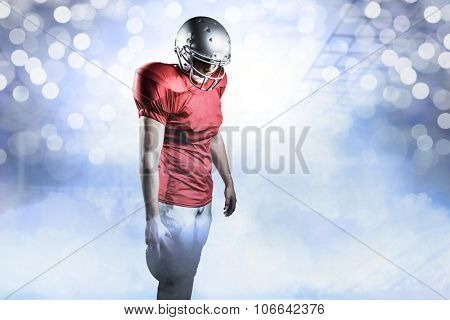 American football player with ball looking down against glowing background