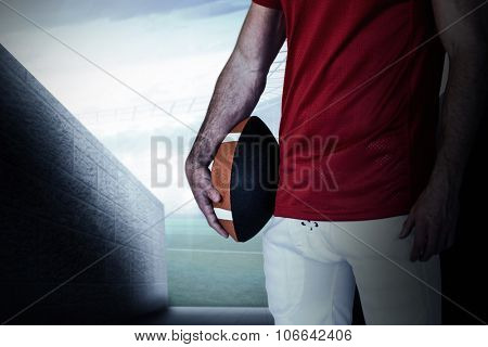Midsection of a player holding rugby ball against sports arena