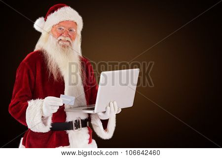 Santa pays with credit card on a laptop against orange background with vignette