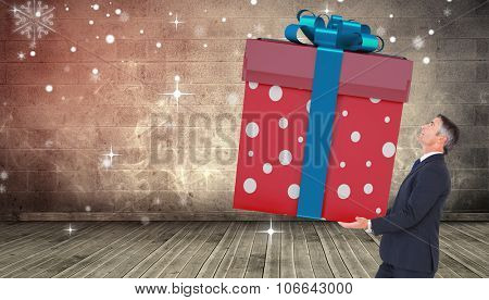 Stylish man with giant gift against grimy room