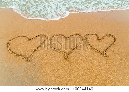 Three Hearts Drawn On Sandy Beach With Wave Approaching