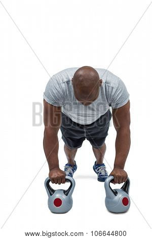 Fit man exercising with kettlebell on white backgroubnd