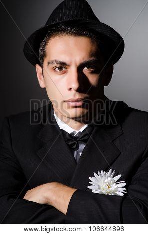 Funny man with flower in dark studio