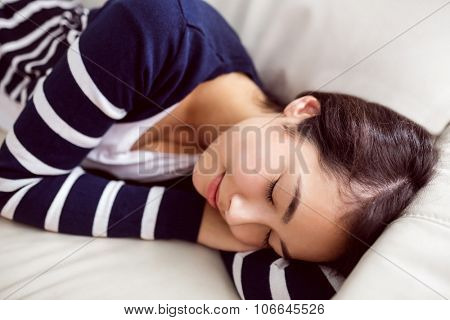 Asian woman napping on the couch at home in the living room